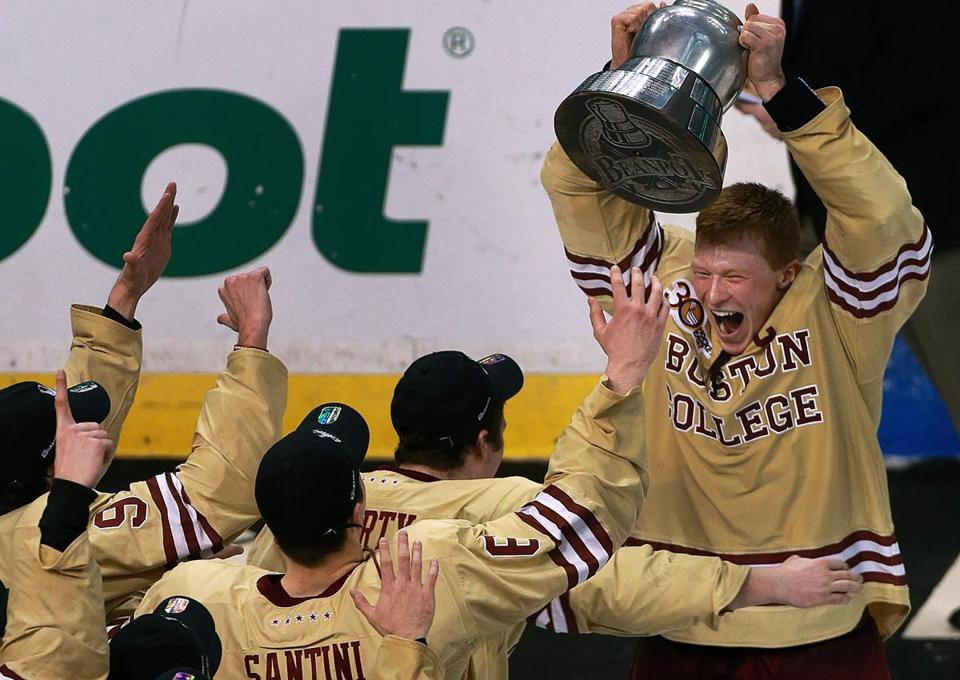 BC senior center and captain Patrick Brown hoisted the Beanpot as he was mobbed by his teammates.