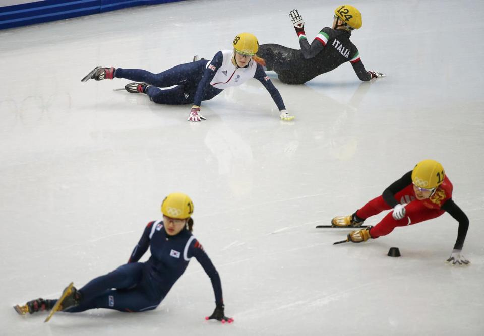 With skaters falling all around her, Li Jianrou (right) makes a sharp turn in the women's 500 meter race.C REUTERS/Marko Djurica )