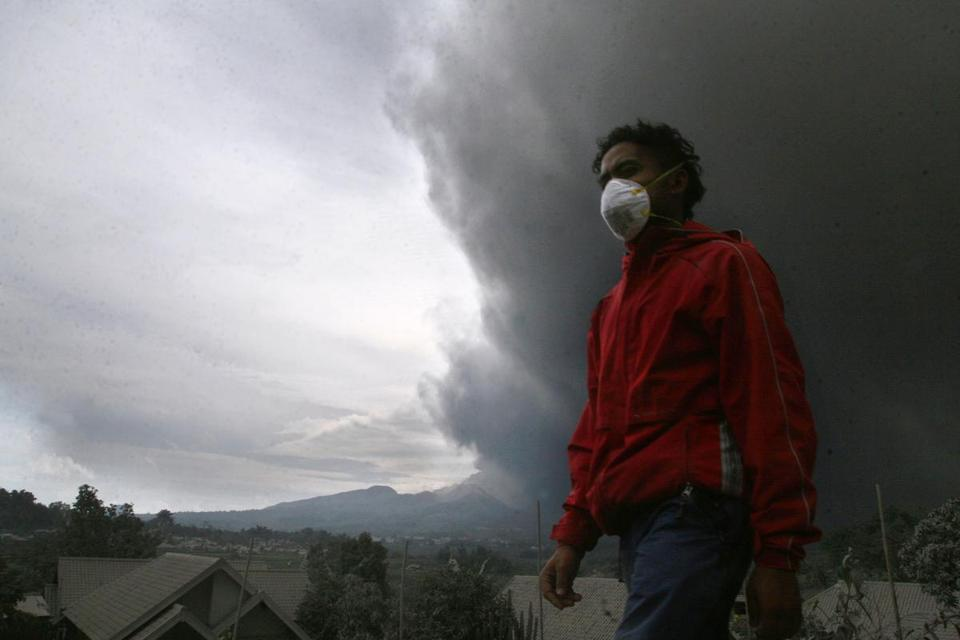 A resident was forced to flee his home under a massive plume of hot ash clouds spewing from the Mount Kelud volcano.