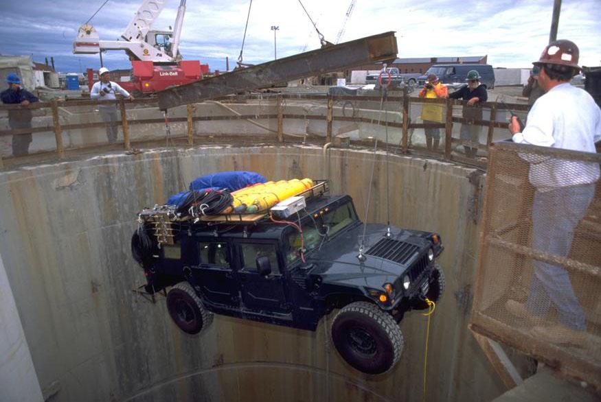 One of two Humvees is lowered into the shaft of the 10-mile-long Deer Island tunnel in 1999.  The Humvees were used by five divers to make their way into the tunnel.