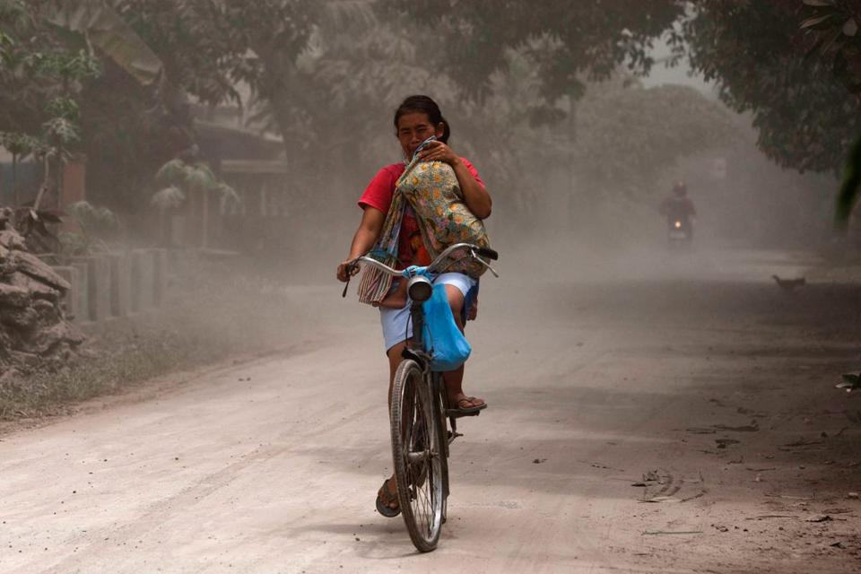 In Yogyakarta, Indonesia, a woman carried her child while bicycling through an area covered with ash from the eruptions of Mount Kelud.