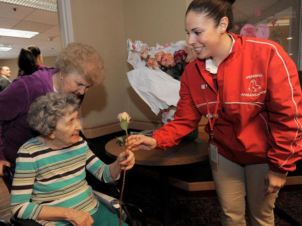 Kali Richards (right), a Red Sox ambassador, presents a rose to a resident at the Life Care Center of the North Shore in Lynn during the team's Valentine's Day caravan and World Series trophy tour.
