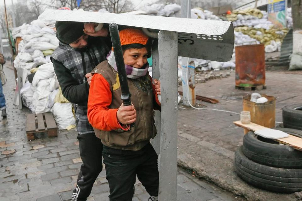 Ukrainian children played with shields near a barricade as the protests continued in Kiev.