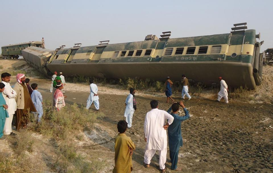 People gathered around a damaged train following an explosion in Kashmor, Pakistan, that injured 20 people.