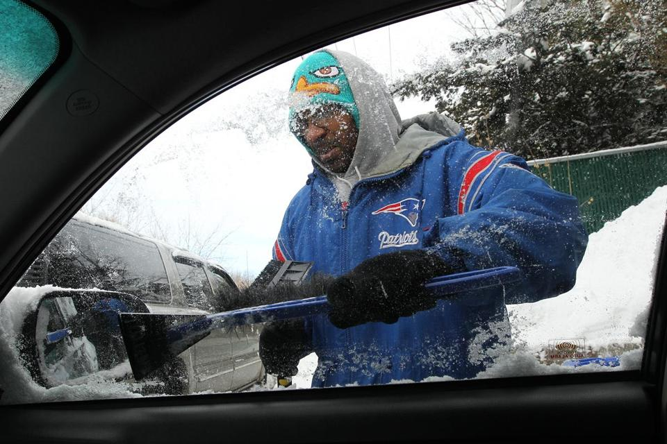 Willie A. Nealy III cleaned his car windows on Harvard Street in Boston, where only 4 inches of snow fell.