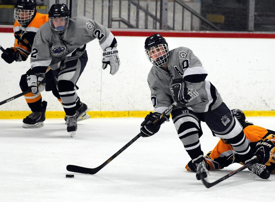 Cohasset's  Chris Cohen passes the puck as Hanover's Mitch Beard falls to the ice attemptin to disrupt the play.