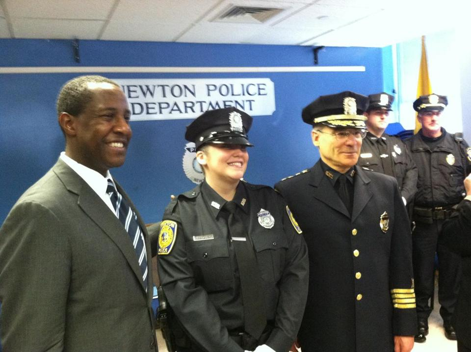 Mayor Setti Warren of Newton (left) conducted the swearing-in of nine new police officers on Friday. The nine will receive 10 weeks of field training before beginning  solo patrols.