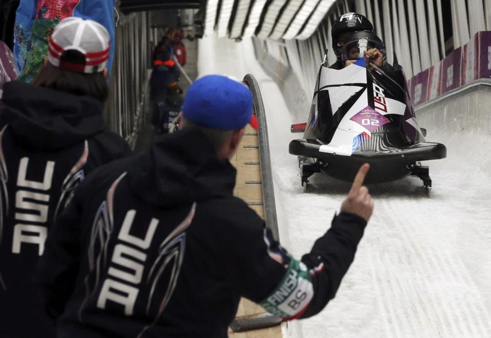 US coaches signal to Elana Myers and Lauryn Williams in USA-1 that, yes, they are in first place after two runs of the women's bobsled.. REUTERS/Fabrizio Bensch