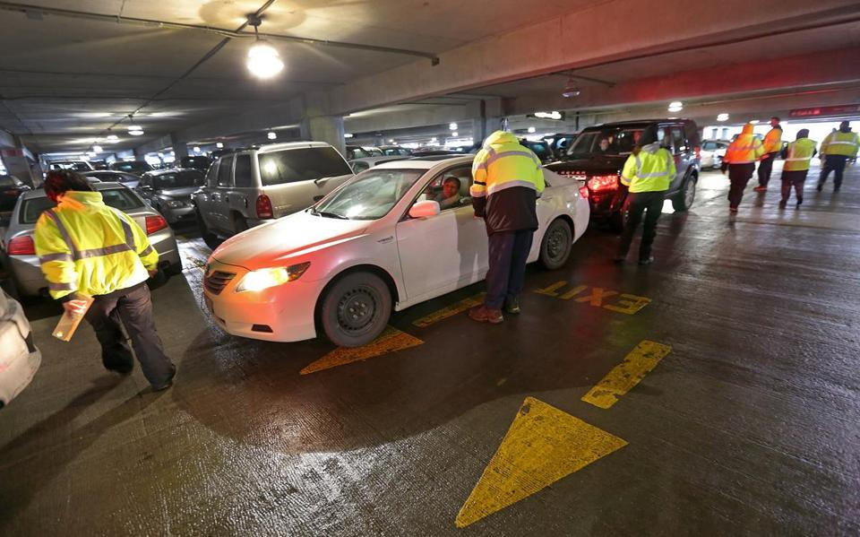 Valets help direct traffic at a crowded Logan Airport garage. The lots can be pushed to their limit during busy times.