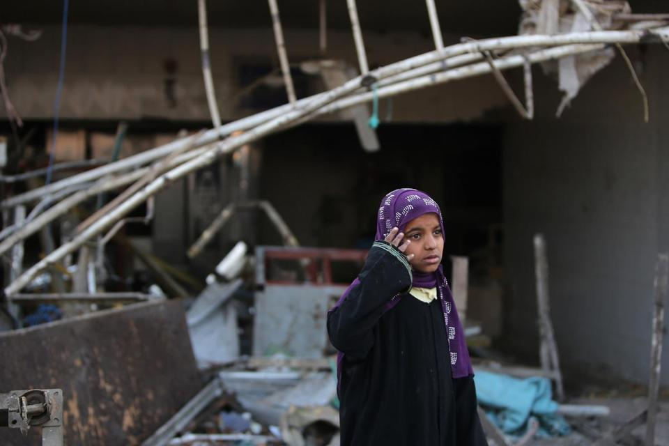 A girl stood near debris following a blast in the Ur district in eastern Baghdad. Bombs killed at least 17 people there.