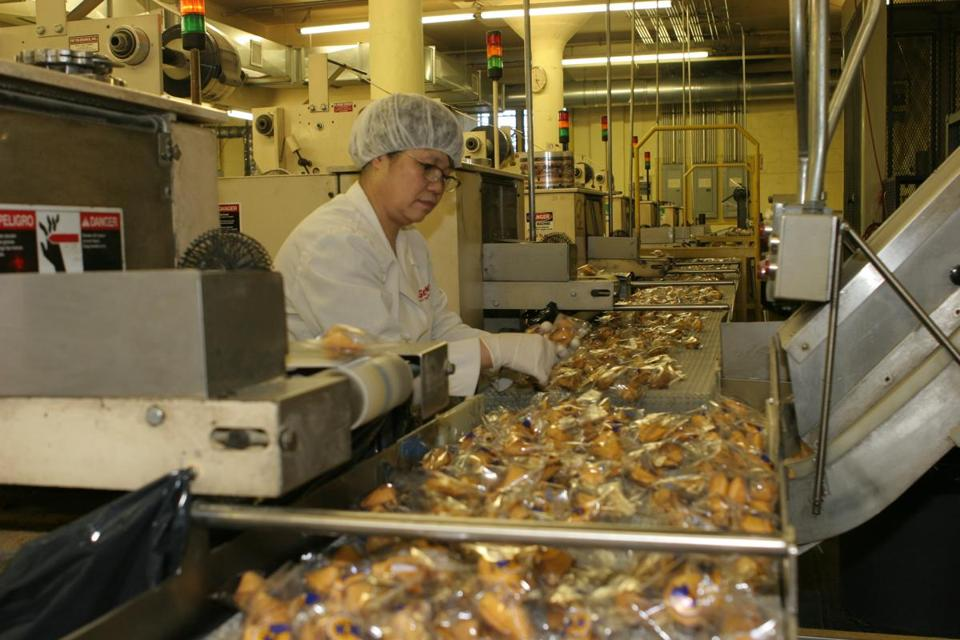 Fortune cookies traveling down the assembly line at Wonton Food's Queens' factory where they produce 4-million fortune cookies a day.