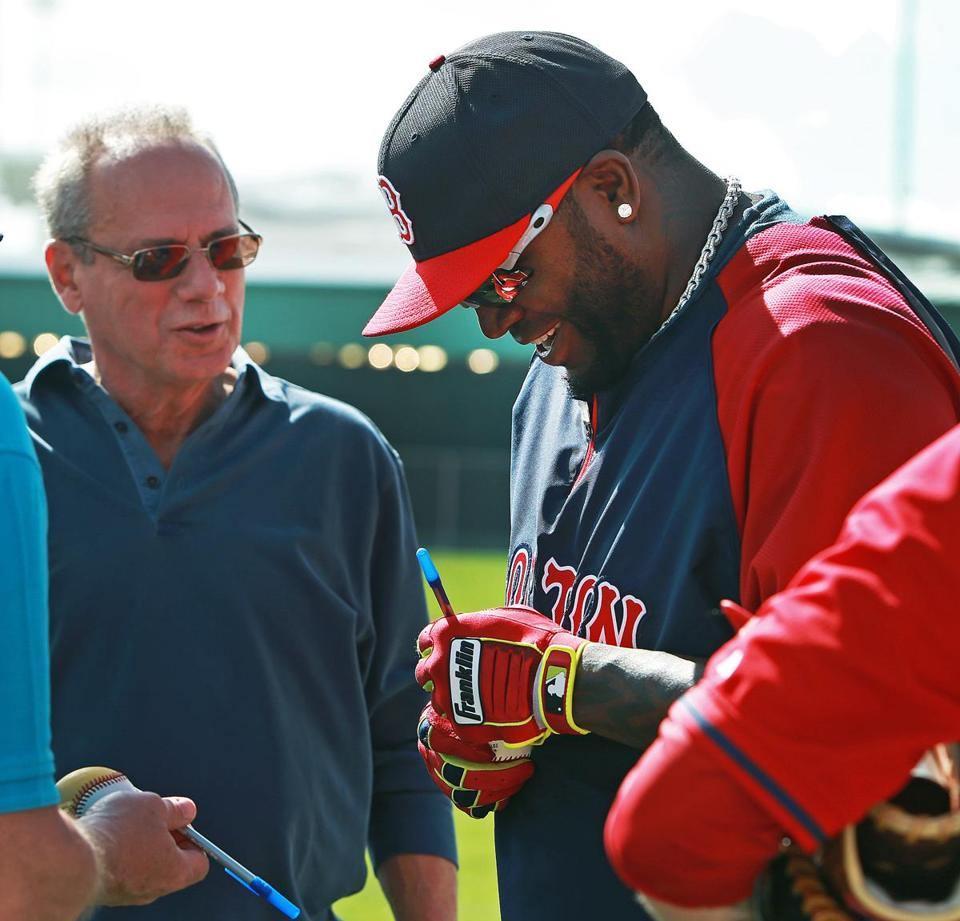 Team president Larry Lucchino (left) looked on as David Ortiz signed an autograph.