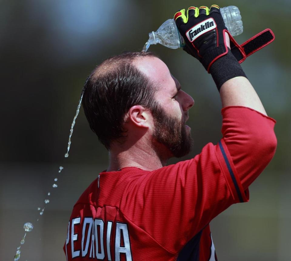 With temperatures in the 80s with high humidity, Dustin Pedroia cools off with some water over his head during batting practice.