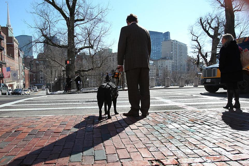 Blind and hearing-impaired, Carl Richardson stood at a crosswalk in front of the State House that has no ramp.