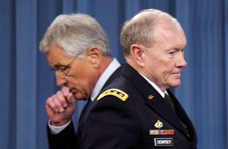 Chairman of the Joint Chiefs of Staff, General Martin Dempsey (right), passed Chuck Hagel during a press conference.