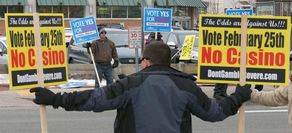 Supporters and opponents of a Revere casino at Suffolk Downs held signs Tuesday.