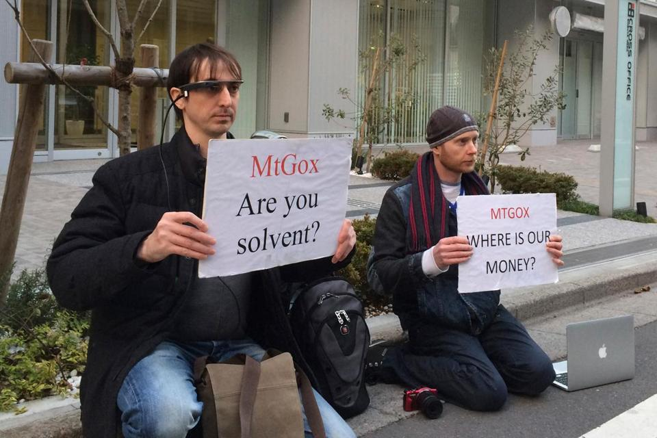 Bitcoin trader Kolin Burges (right) of London and an American, Aaron (only his first name was given), protested outside the office tower housing Mt. Gox in Tokyo Tuesday.