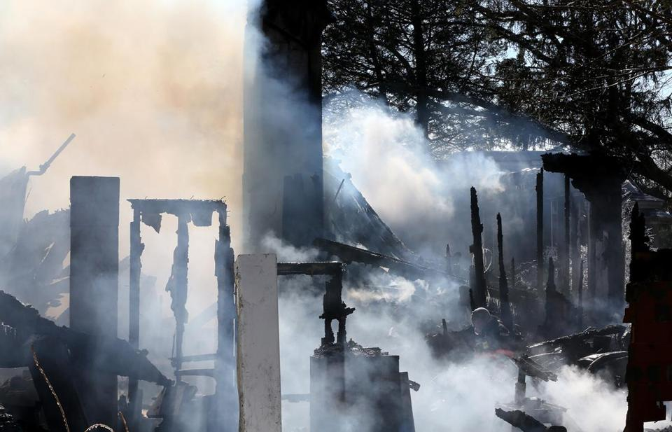 A firefighter moved through the scene of a blaze that killed an elderly couple in Methuen on Wednesday.