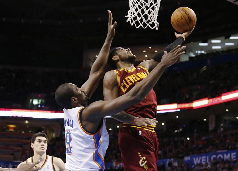 Cavaliers guard Kyrie Irving reached around Thunder forward Serge Ibaka for a second-quarter shot.