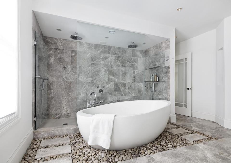 A double shower lined with limestone tiles and enclosed with glass doors is the backdrop for the oval-shaped tub that seems to float on a bed of smooth beach stones in this updated master bathroom.