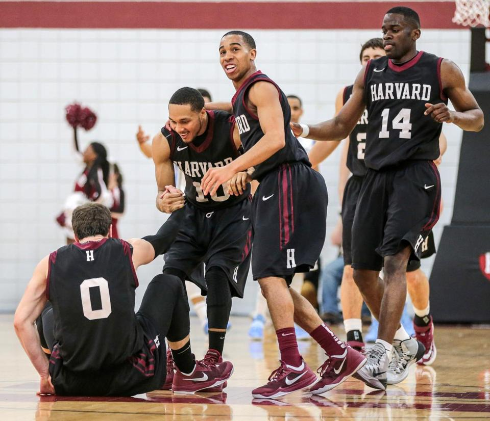 Harvard guard Brandyn Curry (10) is the first to greet Laurent Rivard (0), who was knocked down while scoring.