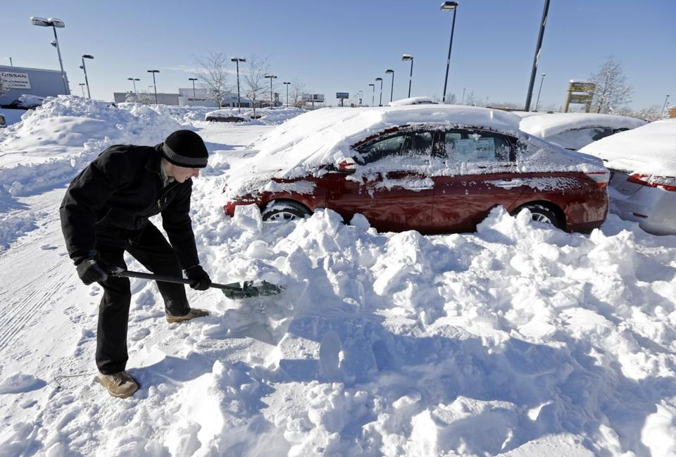 A salesman at a car dealership in Indianapolis shoveled snow. Analysts blame low temperatures and snow for slow sales.