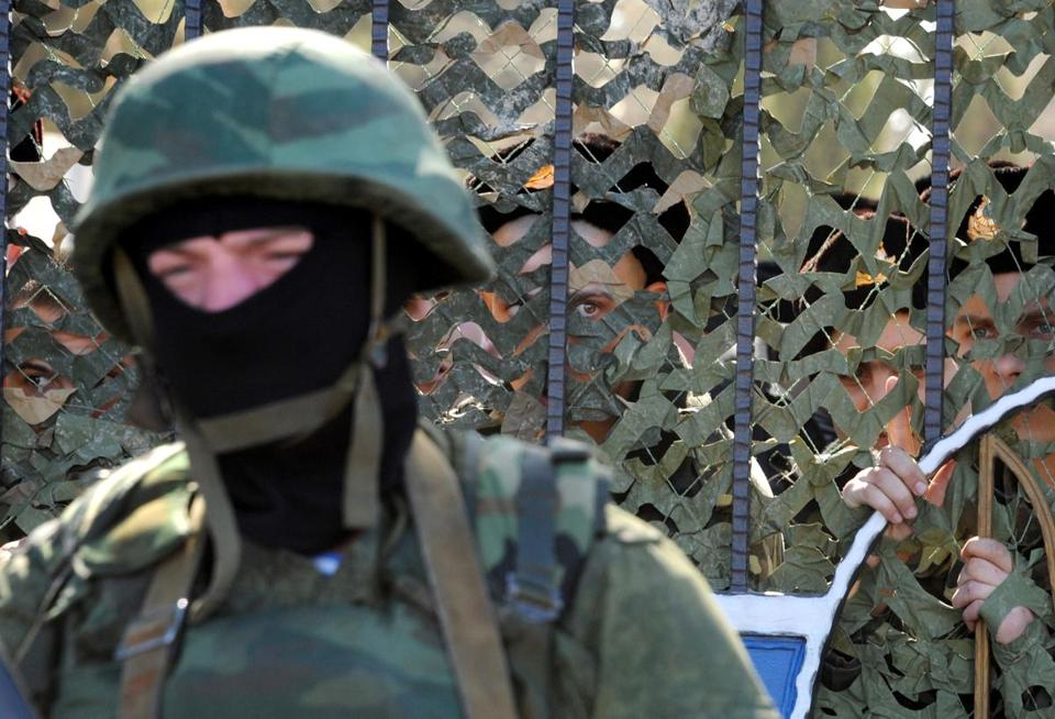 A Ukrainian soldier was on one side of a fence, with unidentified armed men on the other side blocking the headquarters of the Ukrainian Navy in Sevastopol.