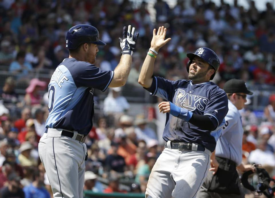 Tampa Bay's David DeJesus (right) is welcomed at home plate by Logan Forsythe after scoring on a single by Matt Joyce in the first inning. (AP Photo/Steven Senne)