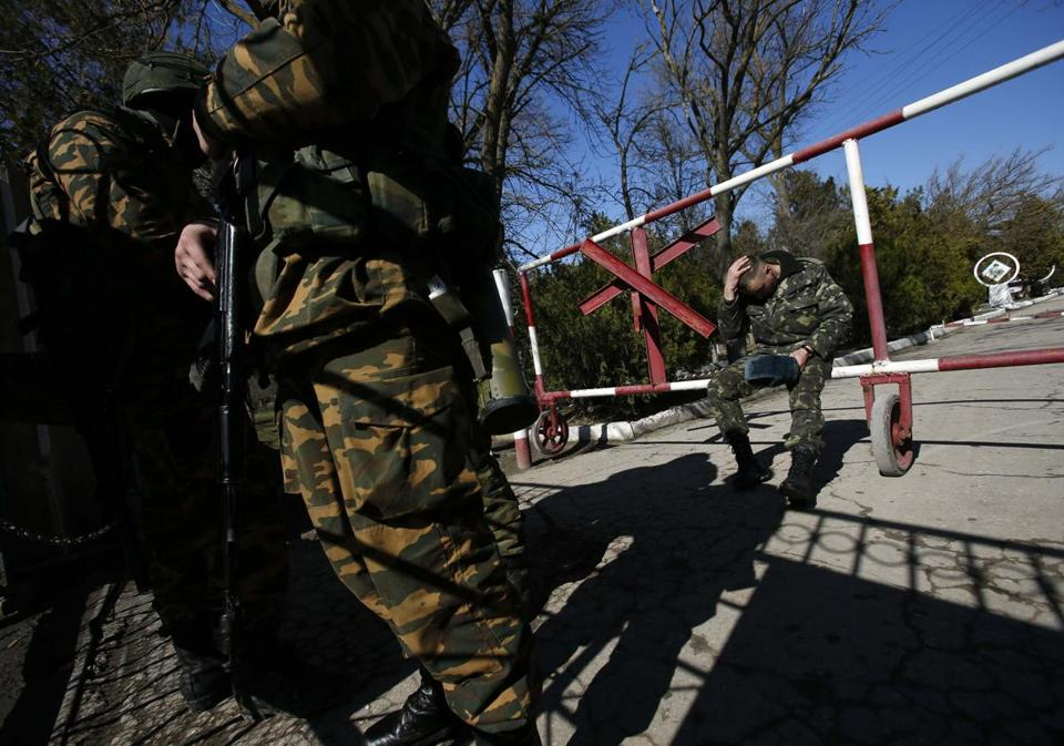 A Ukrainian serviceman (right) sits on a gate as armed men, believed to be Russian soldiers, stand guard inside a Ukrainian military base in the Crimean town of Yevpatoria on Wednesday.