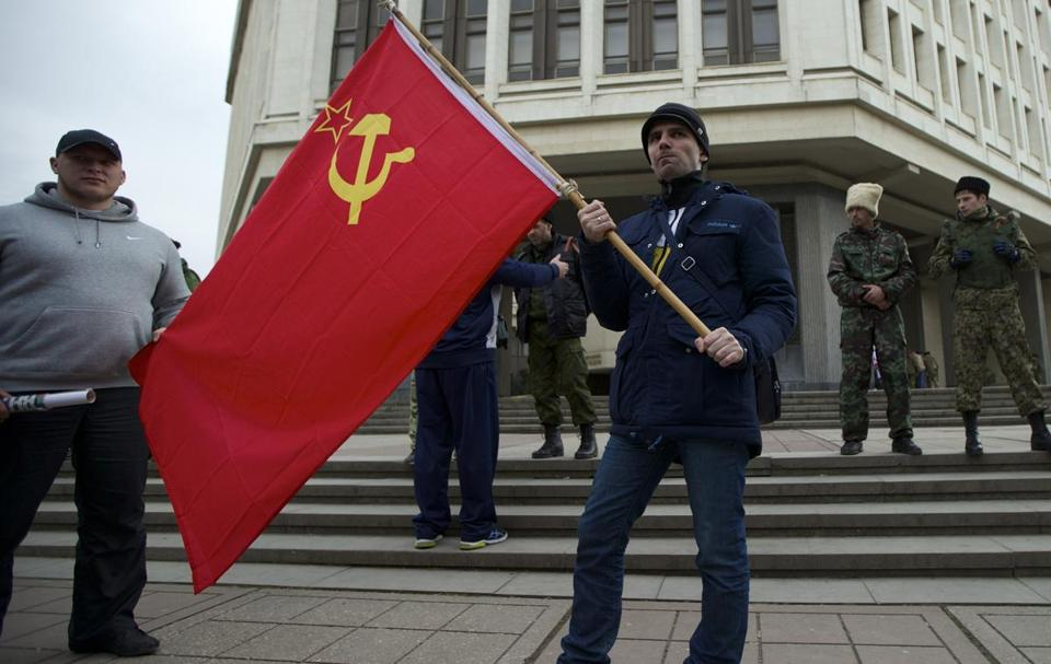Residents of Simferopol, Ukraine, held Soviet flags as a Cossack militia guarded the Crimean Parliament on Thursday.
