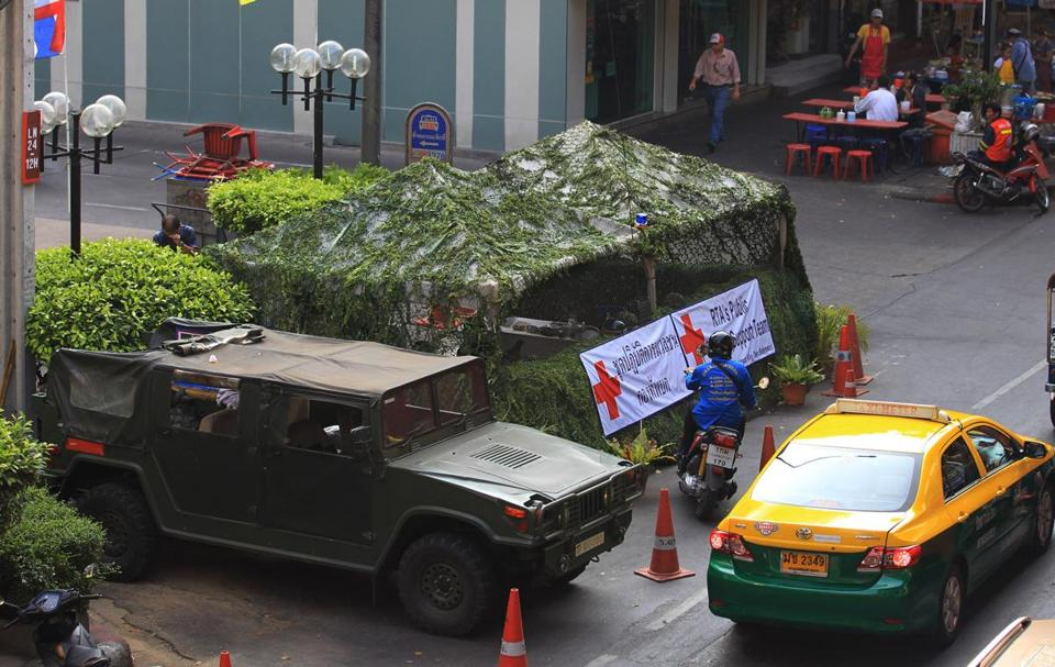 Vehicles moved past an Army bunker Friday in Bangkok. Checkpoints have been decorated to allay civilians' fears.