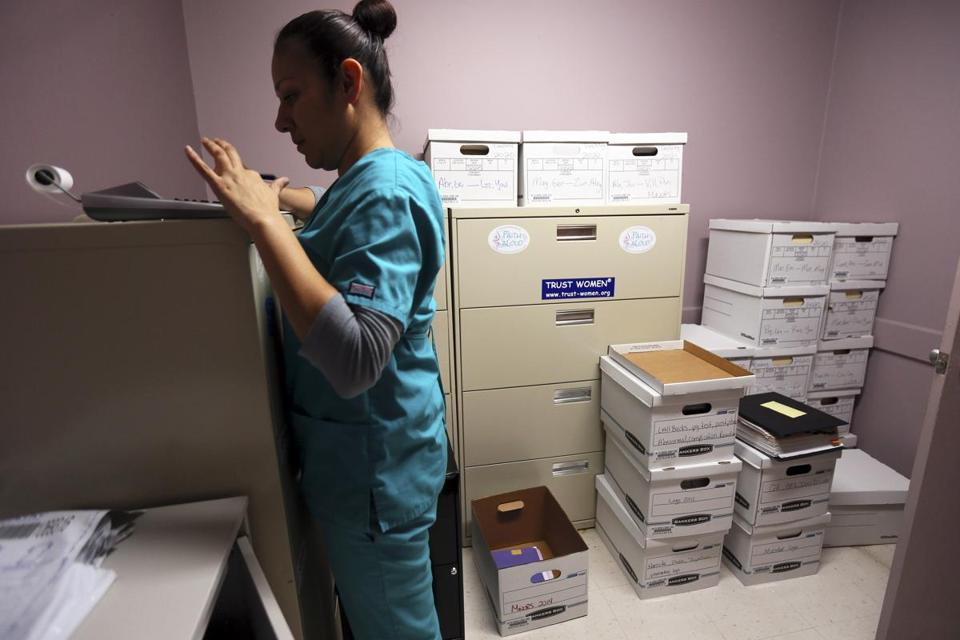 Medical assistant Veronica Hernandez closed out accounting in a room full of files that will be transported for storage, at the Whole Woman's Health Clinic in McAllen, Texas.