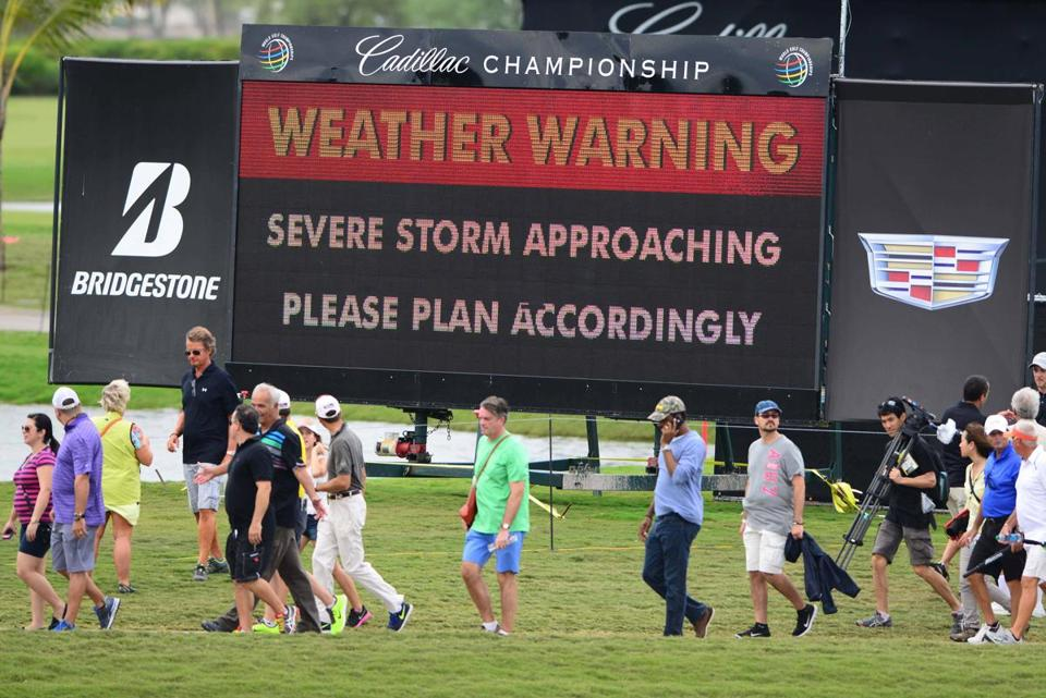 Fans evacuate the Blue Monster at Doral in Miami because of severe weather that stopped first-round play.