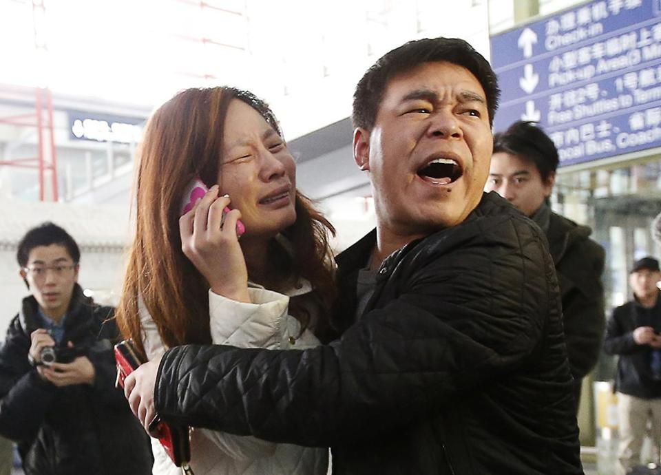 A relative of a passenger who was aboard the flight cried as she talked on her cellphone Saturday in Beijing.