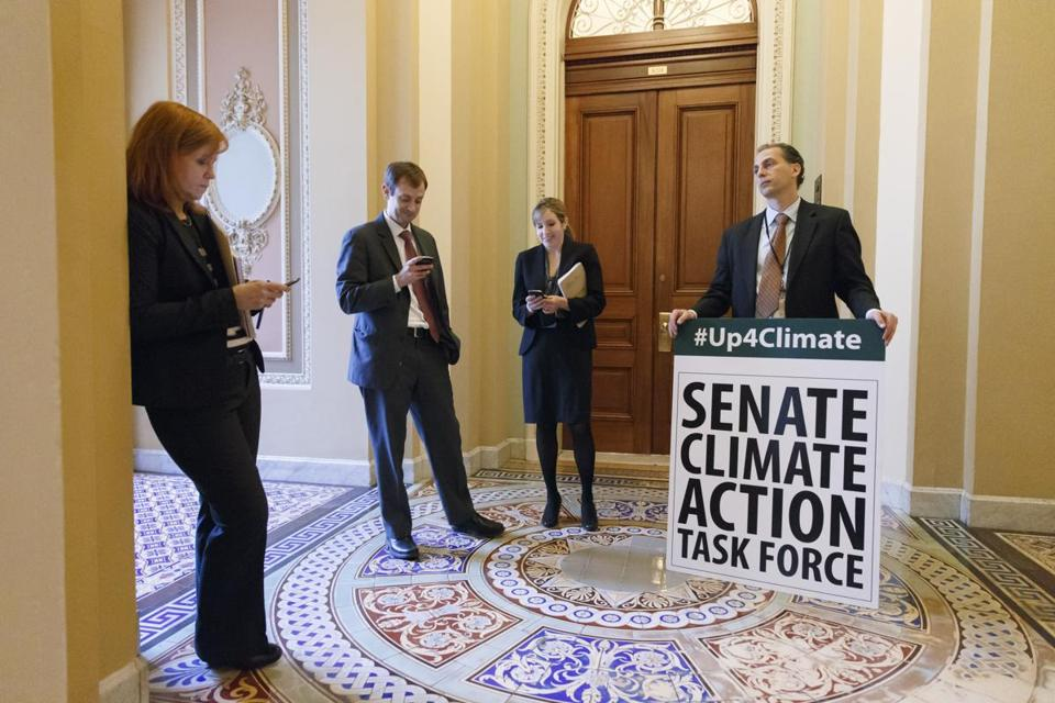 Joe Mendelson, the majority chief climate counsel with the Senate Committee on Environment, right, and other Senate staffers, wait outside the Senate chamber on Capitol Hill in Washington as Democratic senators finished an all-night session.
