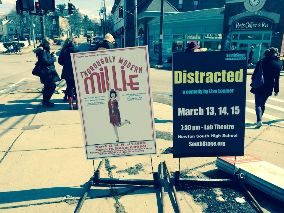 "A sign in Newton Centre advertised Newton North High School's production of ""Thoroughly Modern Millie."