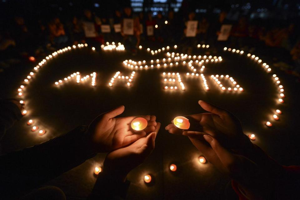 In this March 13, 2014 file photo, university students hold a candlelight vigil for passengers on the missing Malaysia Airlines Flight MH370 in Yangzhou, in eastern China's Jiangsu province. The disappearance of Malaysia Airlines Flight 370 has exposed wide gaps in how the world's airlines, and their regulators, operate. But experts warn this isn�t likely to be one of those defining moments that lead to fundamental changes. (AP Photo/File) CHINA OUT