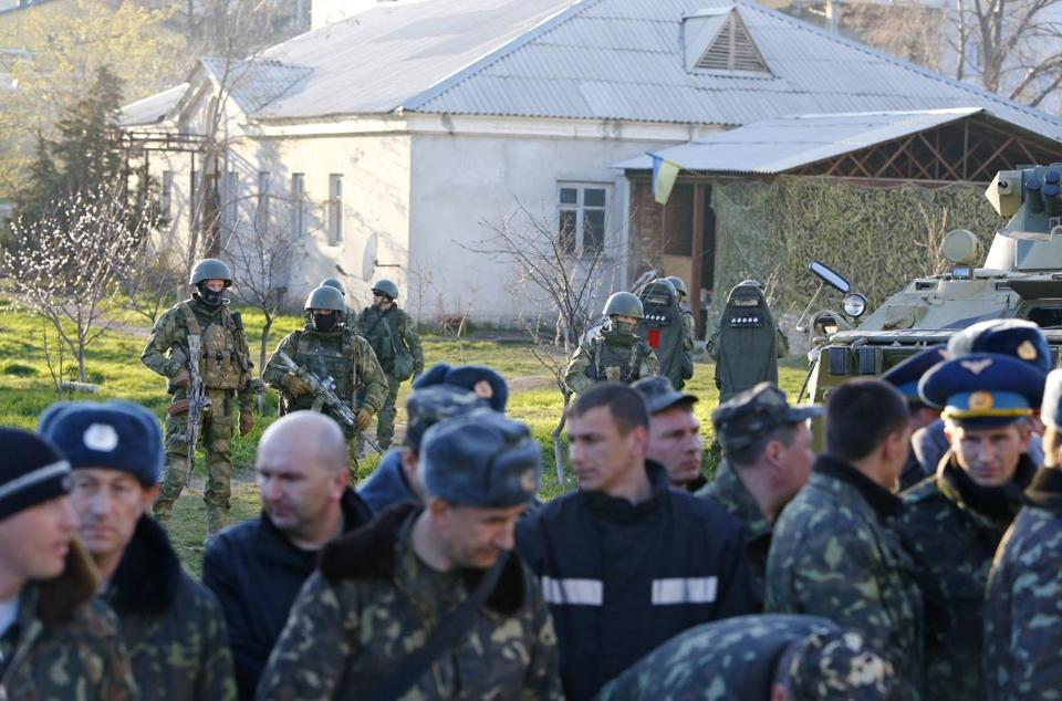 Armed men, believed to be Russian servicemen, stand guard, with Ukrainian servicemen seen in the foreground, at an airbase in Crimea Saturday.
