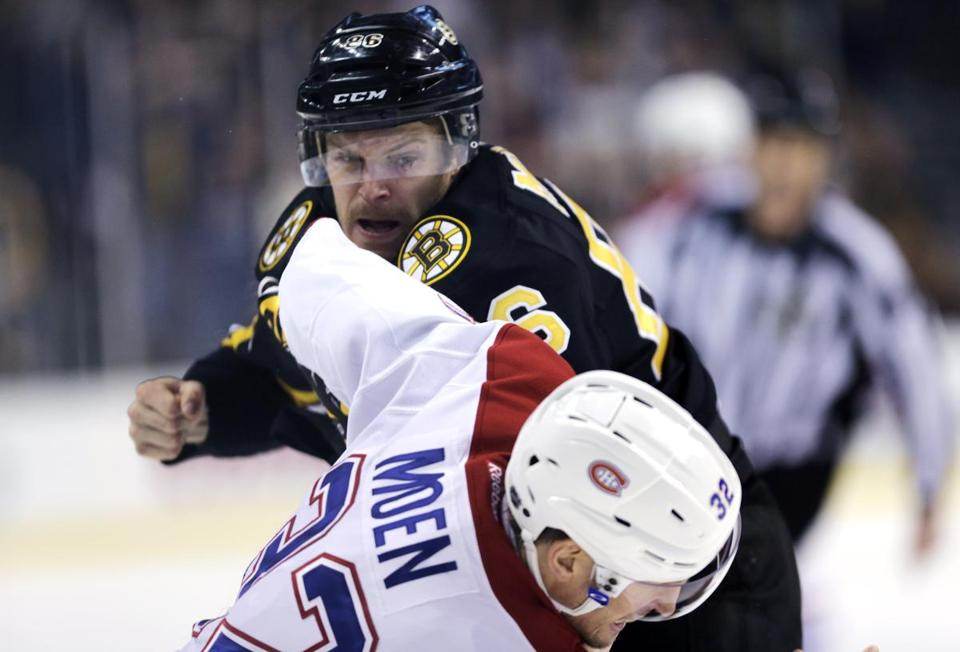 Boston Bruins defenseman Kevan Miller fought Montreal Canadiens left wing Travis Moen (32) during the first period of an NHL hockey game, Monday, March 24, 2014, in Boston. (AP Photo/Charles Krupa)