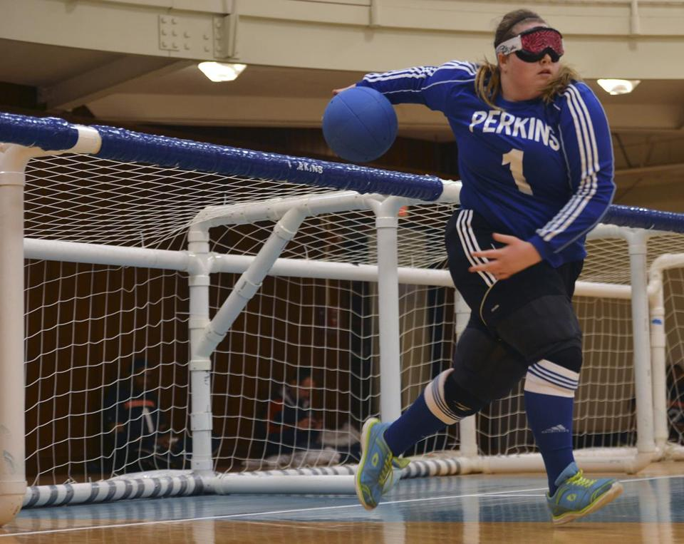 The ball in goalball has bells so the players can keep track of it.  From left, Bella Scott sends the ball; Brendan Flynn (left) and Shae Kelley go for blocks; and Kelley guards the net.