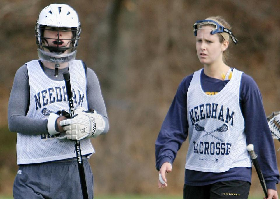 Needham players Annee O'Connor (left) and Catherine Conley walk toward the sideline during a break in action at a recent lacrosse jamboree; below, O'Connor looks to make a save in goal.