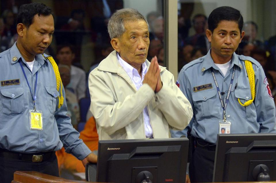 Former Khmer Rouge prison chief Kaing Guek Eav — better known as Duch — greets judges in the courtroom at his trial in Phnom Penh in 2012.