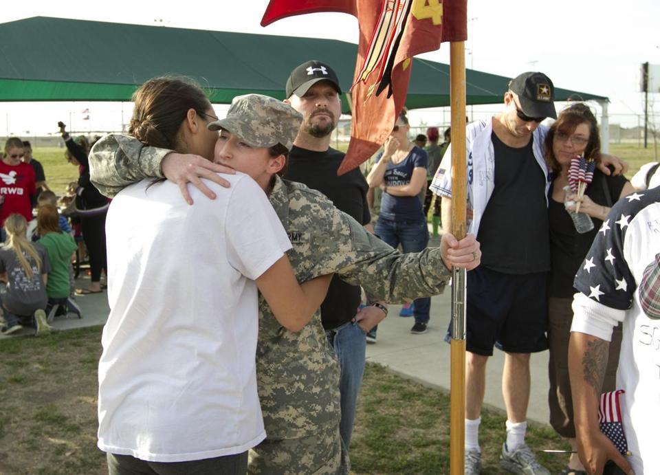 A Fort Hood soldier (at right in foreground)  hugged Specialist Kristen Haley, the fiancee of one of the people killed in the Fort Hood shooting, at a tribute walk for victims in Killeen, Texas, on Friday.