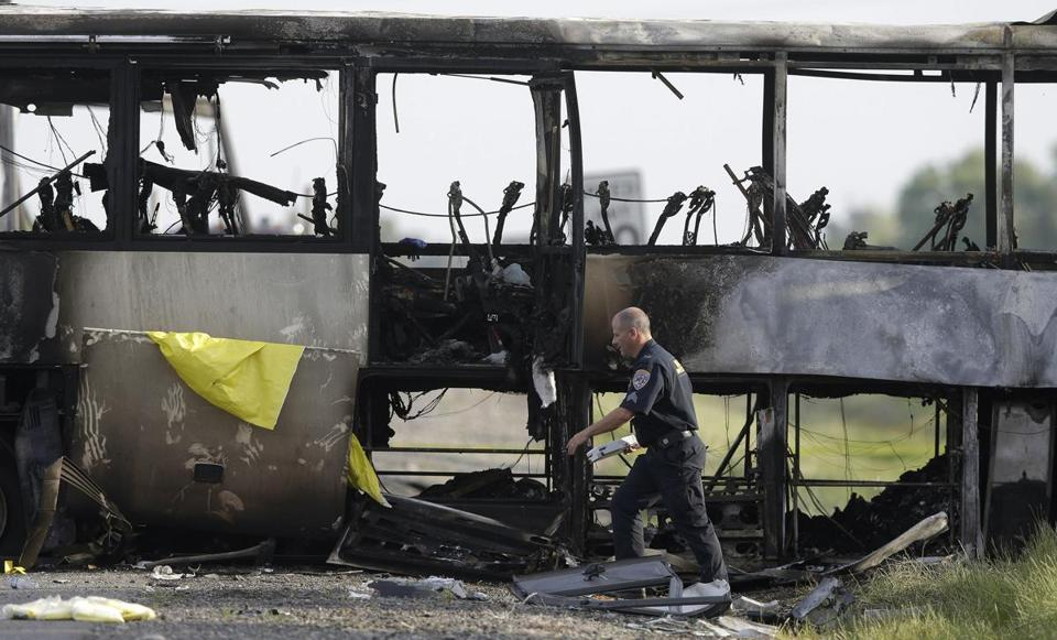 A California Highway Patrol officer walked around the remnants of a tour bus that exploded after it was struck by a FedEx truck. Ten people were killed and dozens injured.