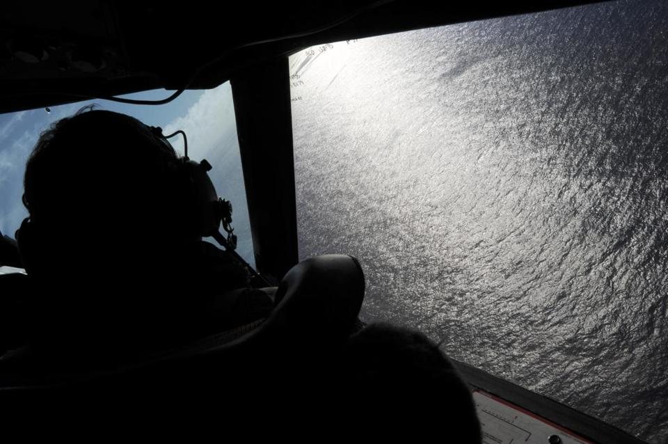 Co-pilot Squadron Leader Brett McKenzie looked out of a window while searching for debris from missing Malaysia Airlines Flight 370, in the Indian Ocean off the coast of western Australia in 2014.