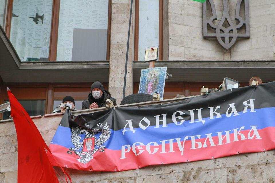 "Pro-Russian protesters have a banner reading ""Donetsk's Republic"" unfurled on a balcony of an occupied regional administration building in Donetsk, Ukraine."
