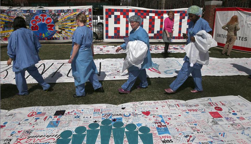 Boston Medical Center staff looked over the Boston Prayer Canvas on display during a flag-raising ceremony Monday.