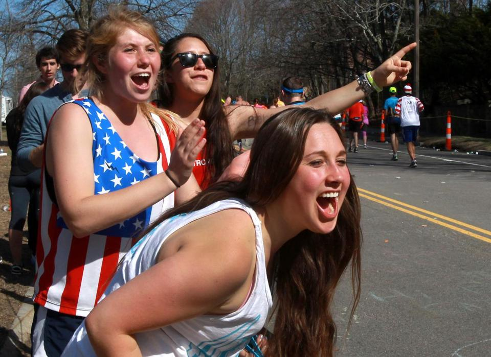Tufts students, from left, Victoria Stoj, Carla Kruyff, and Kate Klots (foreground) on the sidelines of Heartbreak Hill.