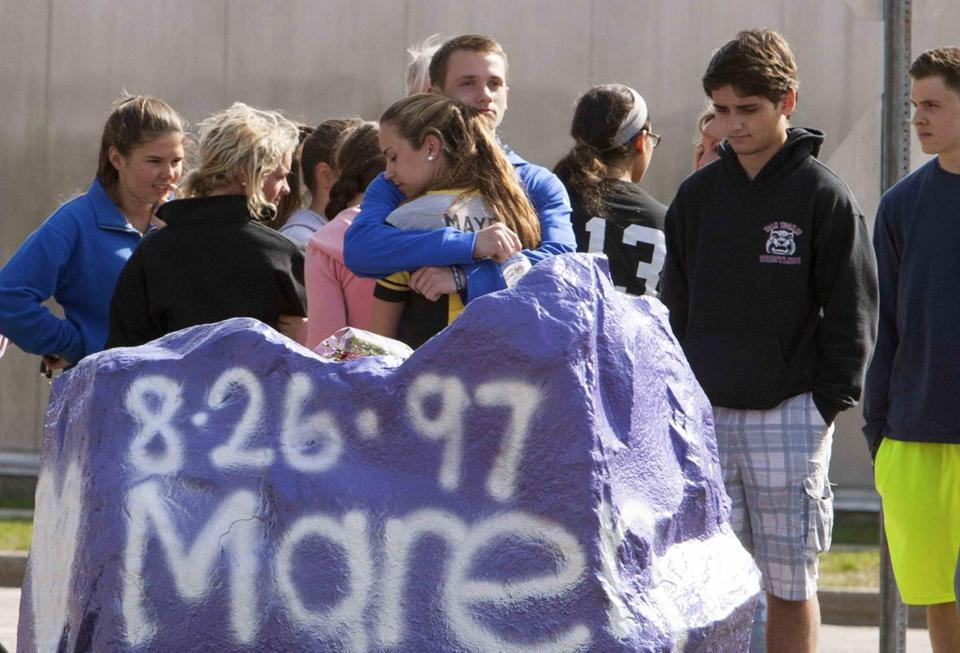 Students mourn in front of Jonathan Law High School in Milford, Conn.