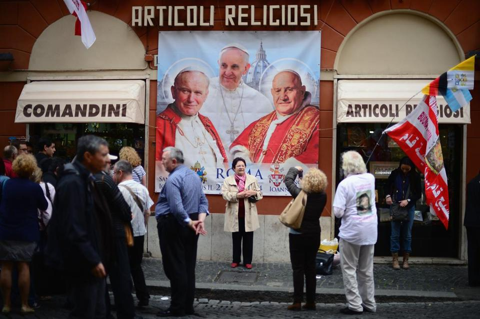 Pilgrims gathered outside a souvenir shop near Saint Peter's Square on Saturday. Pope Francis is set to induct two predecessors into an exclusive club: popes who have been declared saints.